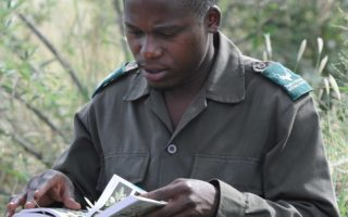 A student reading a book about trees in Southern Africa © SAWC/SAWCT